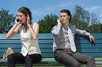 Businessman and women talking on cell phones while sitting on bench outside