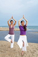 Two women doing yoga on beach