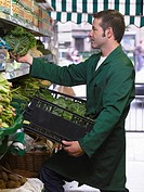 Grocer filling shelves with vegetables