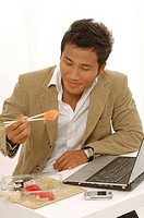 Asian man is eating sushi on his desk