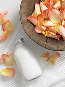Rose petals in a wooden bowl and a cosmetic bottle