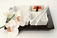 Sushi, chopsticks and orchid blossoms