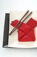 Asian place setting with a red napkin and chopsticks