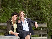 Mother and daughter sitting on bench