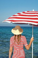 Woman wearing a hat and a red and white sunshade in the water
