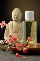 Buddha with a cosmetic bottle and cherry blossoms