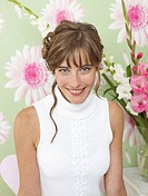 Woman in front of a flowery wallpaper