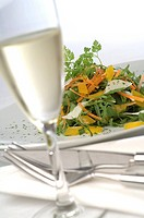 Salad with parmesan and a glass of sparkling wine