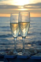 Two glasses of sparkling wine on a chair at the beach in the sunset