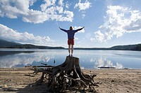 Woman,age 41, standing on tree stump raising her hands to a cloud filled sky
