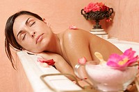 Woman in bath tub with petals, closing her eyes