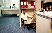 Office worker on the phone hiding from manager (thumbnail)