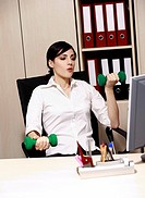 Office worker at desk weight lifting