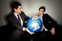 Male and female businesspeople with globe