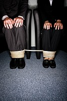 Male and female business people's legs tied