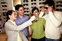 Two couples shopping for sunglasses in store (thumbnail)