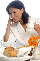 Woman wearing a bathrobe is having breakfast