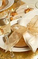Christmas table place setting, napkin tied with a golden ribbon and a glass of white wine