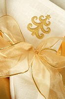 Napkin with a Christmas tree pattern tied with a golden ribbon