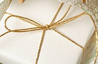 White wrapped Christmas gift tied with a golden ribbon