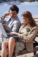 Business couple on beach with cell phone and laptop