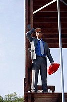 Businessman on life guard stand with life preserver