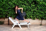 Businesswoman running on chaise lounge (thumbnail)