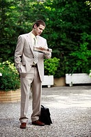 Businessman in garden looking at watch (thumbnail)