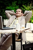 Businessman in garden cafe with laptop (thumbnail)