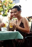 Business couple in garden cafe drinking orange juice