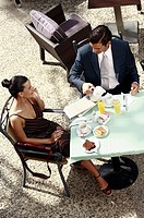 Business couple in garden cafe drinking orange juice (thumbnail)