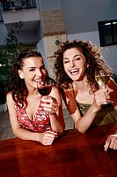 Two women in a bar with wine