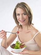 Woman is eating salad