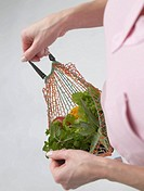 Woman with fruit and vegetables in a string bag