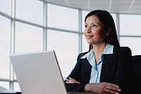 Businesswoman sitting in front of laptop, arms crossed, looking away