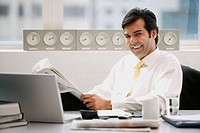 Businessman sitting in office, holding newspaper, smiling
