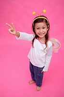 Young girl wearing fairy wings and deely bopper, making peace sign