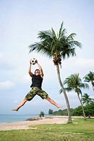Man jumping in air to catch soccer ball