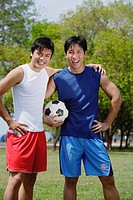 Two men standing together, one holding soccer ball