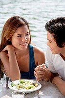 Couple sitting at outdoor cafe, looking at each other