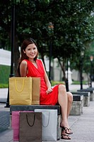 Woman sitting on park bench, shopping bags next to her