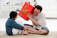 Father and son at home, father holding big gift box