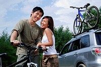 Man on a bike, woman standing next to him, looking at camera