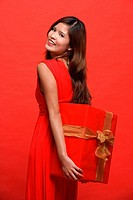 Woman in red dress, holding wrapped gift box, looking over shoulder