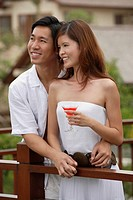 Couple standing side by side on balcony, smiling