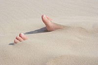 Girl's feets under the sand