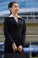 Businesswoman with briefcase, looking away