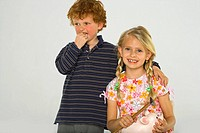 Close-up of a boy standing with a girl holding a piggy bank and a hammer