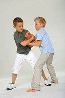 Side profile of two boys snatching a rugby ball from each other