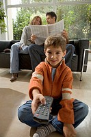 Boy with TV remote control and parents with newspaper in background